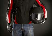 Wall Mural - Biker with helmet in his hands. Dark background