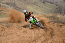 Wall Mural - Motocross rider with a strong slope turns sharply