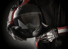 Wall Mural - Motorcyclist with helmet in his hands. Dark background