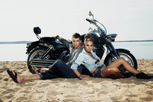 Wall Mural - Boyfriend and girlfriend rider sitting on sand beach by bike